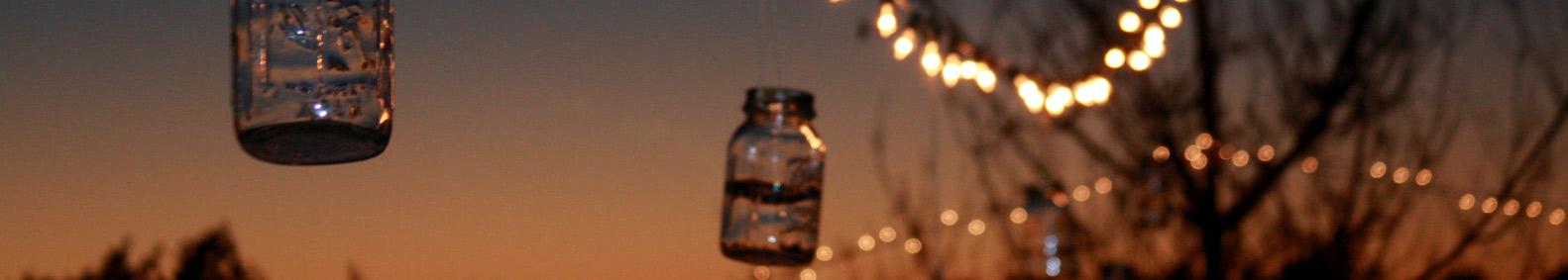 Glass jars hanging from line at sunset
