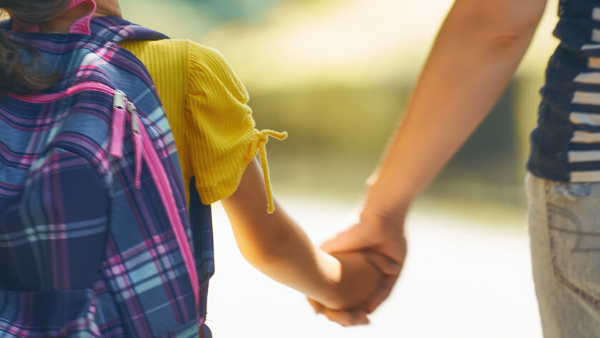 Small child walking hand in hand with parent