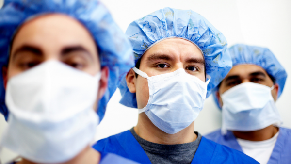 Photo of health care workers in scrubs and wearing masks