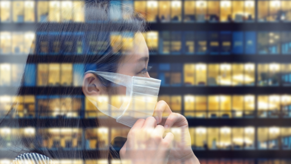 Woman with face mask going back to work with business building reflecting