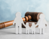 A paper cut image of a family holding hands and standing in front of a gavel.